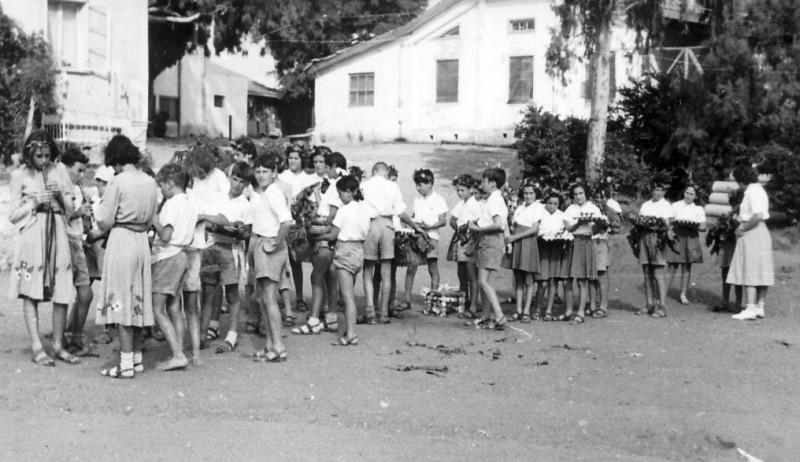תמונה 10- 314 - חג ביכורים שנות ה-40-50 - קבוצת נשר מתכוננים לכניסה לשטח החג - נורית גרינבוים בחל