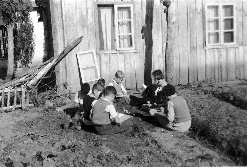 תמונה 4- 225 - ילדי עופר לומדים בגינה מאחורי הכיתה בחצר הקטנה (ברקע - בית ה-ח) - שנות ה-40