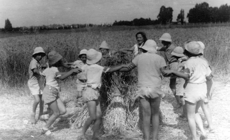 תמונה 9- 215 - קבוצת עופר עם המטפלת דבורה גולביי רוקדים סביב אלומות בשדה - שנות ה-40