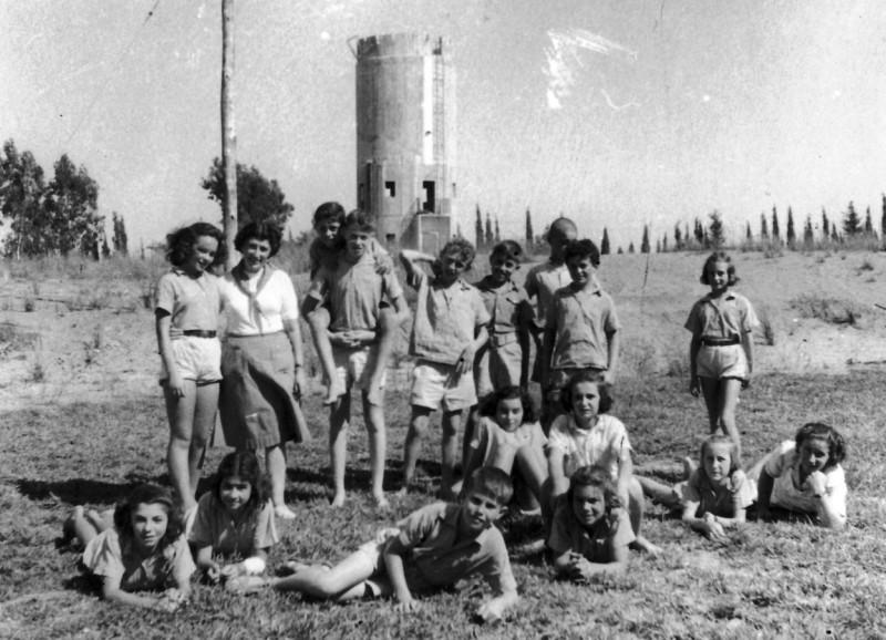תמונה 6- 124 - קבוצת שבלים עם המורה ריקל לב והמטפלת אתיה הניג - על הדשא לפני מגדל המים
