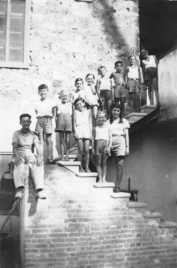 תמונה 12- 220 - ילדי קבוצת אורן עם ריקל לב והמורה אלכס על מדרגות בית הקומותיים הראשון-בית הילדים
